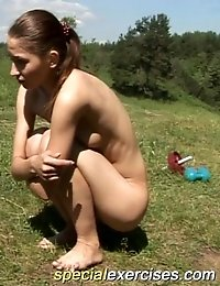 Horny coach makes naked gymnast exercise outdoors