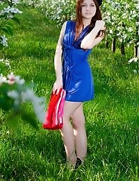 Charming Redhead Girl With Bow In Hair Stripping And Spreading Legs Among The Flowering Trees.
