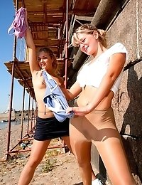 Two playful outdoor gymnasts in pantyhose