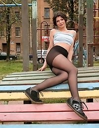 Girl in black pantyhose does gymnastics outdoors