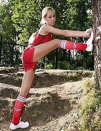 Blonde in tights stretching and flexing outdoors