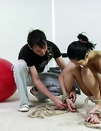 Unclad gymnast exercises with roped limbs