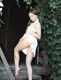 Perfect Brunette Seems To Feel Quite Comfortable As She Is Sitting On The Wooden Stairs Of Her Grand