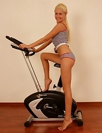 Blonde sports girl exercycling and stretching