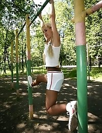 Blonde Emilias in pantyhose doing stretching exercises outdoors
