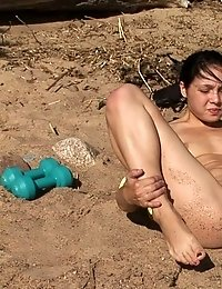 Naked sports brunette works on the beach