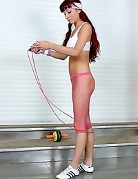 Redheaded girl in red pantyhose jumping with jumping rope