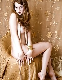 Fabulous Nude Angel Is Posing On The Chair On The Golden Background In A Very Fascinating Way.