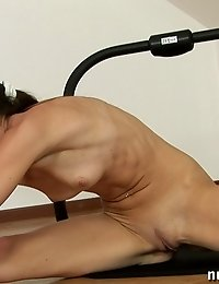 Slender naked fitness wench exercises with a rocker