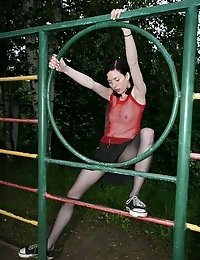 Sports missy in black tights exercises outdoors