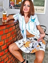 Hot brunette Lily in brown fashion pantyhose posing on bar
