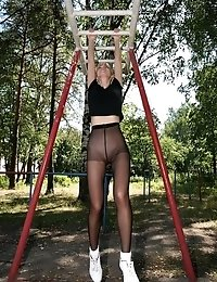 Blond in black tights flexing in the yard