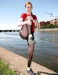 Redheaded Nimfa in pantyhose doing aerobics by the riverside