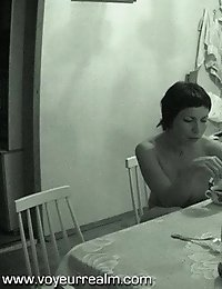 Nude brunette woman having her breakfast