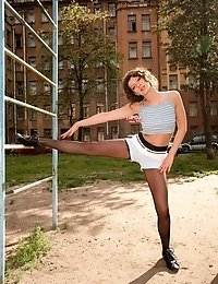 Tall pantyhose gymnast exercises in the open air