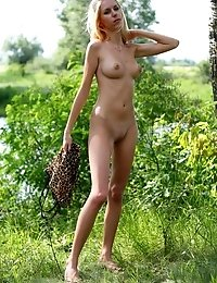 Charming Blond Is Standing In The Forest Near A Lake And Looks Like A Real Lioness In Leopard Dress,